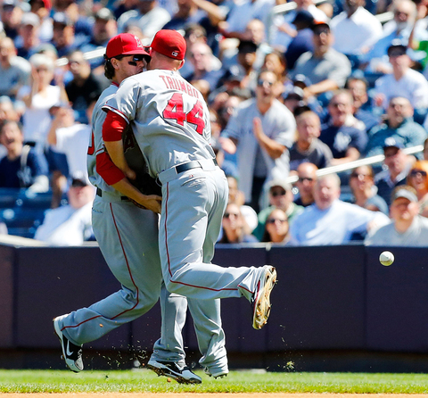 Grant Green and Mark Trumbo of the Los Angeles Angels collide and miss a ball