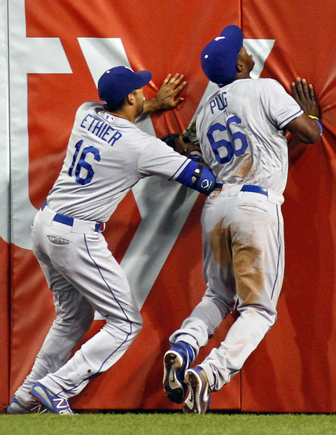 Andre Ethier of the Dodgers collides with teammate Yasiel Puig after making a catch