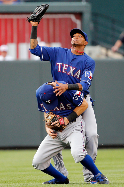 Engel Beltre of the Texas Rangers almost collides with teammate Ian Kinsler  while catching a ball