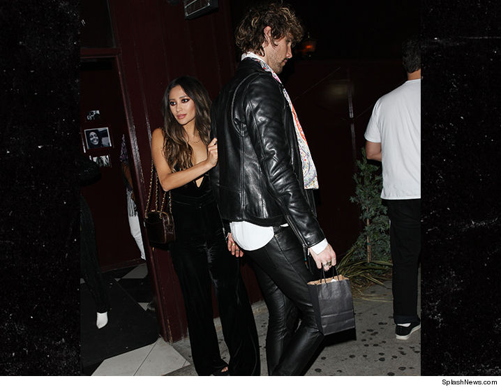 Shay Mitchell walked out of Jessica Alba's birthday party with a present of her own, a tall hunk in black leather.
