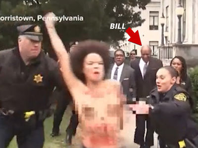 Topless Protester Charges Bill Cosby on His Way into Court