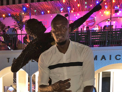 Usain Bolt Parties with Famous 'Bolt' Statue, Made from Real Bolts!