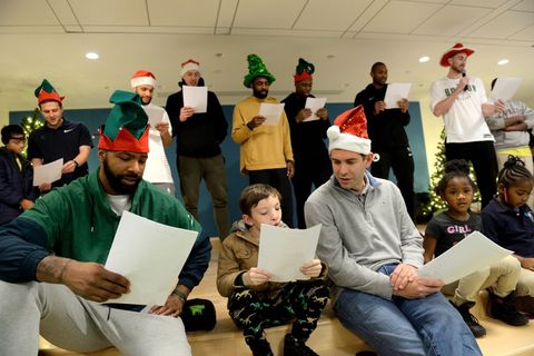 Coach Brad Stevens sings holiday songs with the kids as his team Matthew Reynolds, Kenny Graves, Daniel Thiels, Kyrie Irving, Guerschon Yabusele, Al Hereford and Gordon Hayward back him up.
