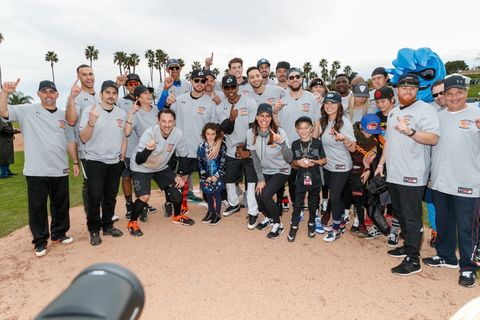Players pose for a team photo on the field at a charity softball game to benefit 'California Strong' at Pepperdine University.